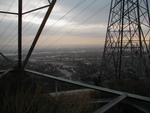 A shot from the toll road, between the legs of a cross-country power transmission tower.